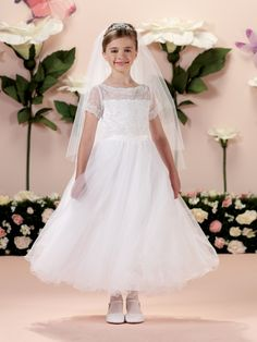 Satin, tulle and lace tea-length full A-line dress with illusion and lace short sleeves, allover hand-beaded lace appliqué bodice features a front and back illusion bateau neckline, satin waistband, back covered buttons, multi-layer tulle skirt finished with wire hem, suitable as a First Communion dress.Sizes: 6 - 14