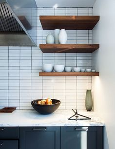 Walnut shelving offers a rustic contrast to the kitchen's glazed subway-tile backsplash by Nemo Tile. The ceramics by Pieter Stockmans and Christiane Perrochon and the forged triangle dinner bell are all from Calvin Klein Home.