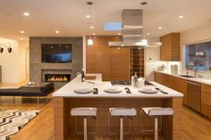 The quartz-topped island in the kitchen includes a casual dining space. Dining Area, Dining Rooms, Concrete Patio, Custom Cabinets, Kitchen Living, Open Concept, Home Values, Great Rooms, Family Room