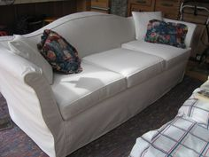 A white denim slipcover is so fresh and easily laundered with bleach. By Sew Like The Wind.