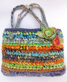 This happy, colorful mini-tote is ooak. It is hand crocheted from recycled materials, plarn (plastic bags yarn) and reused fabrics stripes that I make myself. 3 colorful fabric flowers, hand sewn, are attached to the front. I just love how all these colors come together! Dimensions (appx): 9 tall x 3.5 wide x 13 long. 4 x 12 straps hang Every bag that I crochet is OOAK, as I use different fabrics to make it. Easy care: Gentle wash cold, lay flat to dry. I crochet my bags in...