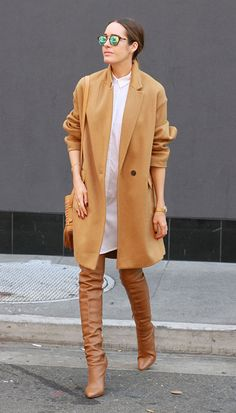 camel colored winter coat with over the knee brown boots and mirrored sunglasses