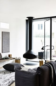 Modern living room with suspended fireplace, black sofa, and minimal details