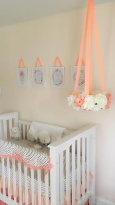 Beautiful peach, cream and gold nursery for a little girl. The floral nursery mobile and gold dot crib bedding are stand outs.