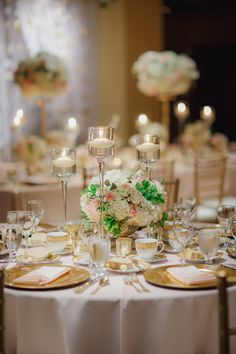 I like the low flower arrangements with floating candles!  Photography: Yvonne Wong Photography - yvonne-wong.com  Read More: http://www.stylemepretty.com/northwest-weddings/2014/04/08/glamorous-gold-ballroom-wedding-in-portland/