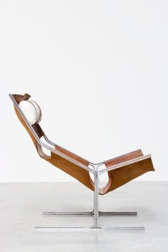Modernist dutch lounge chair made by AP originals Abraham Polak furniture industry Circa 1960 Original cognac saddle leather suspended and supported by a brushed steel frame Pillow made of white canvas | http://www.furniture-love.com/browse.php | From selection of important 20th century modern furniture