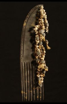 Papua New Guinea | Comb from Moi Biri in the Collingwood Bay region | Turtle shell decorated with hells, seeds and natural fiber | It would have been worn horizontally with the shells and other attachments swinging below