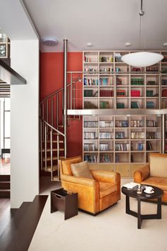 This is an incredible home library.  It's just got so much going for it: comfy leather chairs, floor to ceiling bookshelves, and a discreetly placed spiral staircase to name a few.