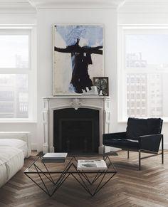 Sala de estar encantadora com mesa de centro, piso de parquet, lareira e poltrona preta com sofa branco da decoradora Katty Schiebeck