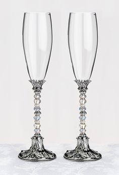 This pair of elegant beaded charm wedding champagne flutes  features a series of silver and clear beads decorate the middle portion of the stems.  To personalize this glass set, you can easily remove the beads and replace them with your own special beads.  Simply unscrew the base from the threaded rod.  The threaded rod has a 3mm diameter, so your beads will have to be able to slide onto that.We sell other bead colors for an additional charge that will fit onto these glasses - available…
