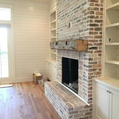 Gorgeous brick fireplace with wood beam mantle & white flanked built-ins.