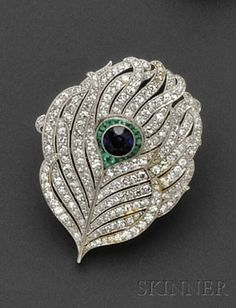 Art Deco Platinum Gem-set Brooch, designed as a peacock feather, bezel-set with a sapphire measuring approx. 5.40 x 5.20 x 3.70 mm, framed by fancy-shaped emeralds, further set with single-cut diamond melee, approx. total diamond wt. 1.80 cts., millegrain accents, lg. 1 5/8 in.