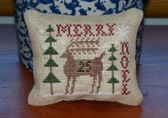 Cross stitch Christmas mini pillow or pin cushion with reindeer.  Done on linen.  Design by Homespun Elegance.