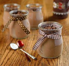 Postre de chocolate en un pequeño frasco de vidrio sobre una mesa marrón Foto de archivo