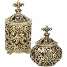 "Set of 2 conisters in distressed gold with openwork detailing and fleur-de-lis finials.   Product: Small and large boxConstruction Material: ResinColor: Distressed goldFeatures: Perfect finishing touch to any decorDimensions: 8.25"" H x 5"" Diameter (large)"