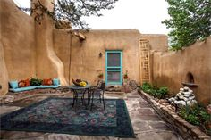 A Small Courtyard In Santa Fe, New Mexico - This enclosed patio displays a lot of the elements together that create a Southwest landscape design. The Spanish style which influences a lot of Southwest gardens is also obvious in this garden. The blue and brown tones always work well together. Almost every element and piece of decor in this courtyard garden could be used in another setting to create this same style.