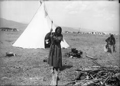 Mary Walk in Water (also known as Mary Inhoosta Woodcock), a Native American woman on the Flathead Indian Reservation in western Montana, chops a log with an ax in front of a teepee - Boos - 1900s
