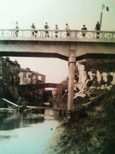 Il ponte della Vittoria visto dall'argine del fiume Pescia. Sulla destra donne che stendono il bucato sull'erba e su corde tese.