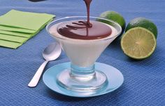 Na foto, o mousse de limão com calda de chocolate está disposto em uma taça pequena de vidro. A calda de chocolate está sendo despejada sobre o mousse. A mesa está coberta com uma toalha azul e na decoração está uma colher e limões fatiados ao lado.