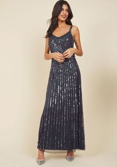 In the way that you're allured by to the most luxurious fetes, others will be drawn to your sophistication in this navy gown at such occasions! Bedecked from shoulder straps to floor-length hem in rich silver sequins and beads, this stunning number is nothing less than absolutely captivating.