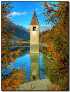 Reschensee, Italy  this city was flooded by what is now Lake Reschen in the 1950s. The artificial lake covers the abandoned villages of Graun, part of Reschen, and others. The top of the 14th-century church tower is still visible. In winter, when the lake freezes, the tower is reachable by foot. A legend says that during the winter one can still hear church bells ring. I want to scuba dive in the lake!