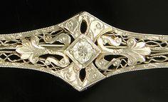 Edwardian Era brooch set with a sparking Old European Cut diamond. Open filigree work in 18kt white gold
