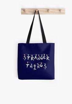 """Stranger Things"". You recognize this from Will's Mother's Wall! For who loves Eleven (Millie Bobby Brown), Mike (Finn Wolfhard), Dustin (Gaten Matarazzo), Lucas (Caleb McLaughin), Will (Noah Schnapp), Joyce (Winona Ryder), Chief Hopper (David Harbour). #strangerthings, #netflix #strangerthingsfan #nerd #geek #friendsdontlie #eleven #mike #dustin #lucas #chiefhopper #hawkins #upsidedown #dungeonsanddragons #totebag #bag #fashion #ootd #women Stranger Things Lights, Don T Lie, Xmas Lights, White Tote Bag, Winona Ryder, Nerd Geek, Millie Bobby Brown, Dungeons And Dragons, Classic T Shirts"