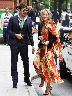 Kate Moss in a summery red and yellow floral dress and black blazer with husband Jamie Hince