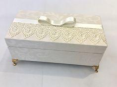 Caixa com pés dourados, detalhes em renda e pérolas. Possui mensagem impressa colada na tampa interna e santinha em gesso com pérolas. Medida da caixa 20x10