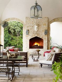 The classic design of this porch perfectly complements the home's Italian villa-inspired style. Rounded archways and heavy stone surfacing create a comfortable, rustic setting. Plenty of lighting and a large fireplace ensure gatherings can last well into the night.