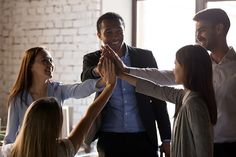 Excited multiracial team give high five, happy african and caucasian office people group celebrate good work results, motivated employees workers engaged in unity help support, teambuilding concept ,