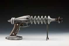 """A great 'retro' Metal Sculpture  """"Ray Gun""""  Created by Scott Nelles  Inspired by extraterrestrial contacts, this ray gun is hand cast in bronze and aluminum. Each ray gun has a spring trigger and a display prop. Cool!   http://www.nellesstudios.com/index.html"""