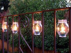 Tolle Balkonidee: Kerzen in kleine Gläser und an die Veranda befestigen!