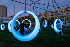 SWING TIME is an interactive playscape composed of 20 illuminated ring-shaped swings. The installation activates a temporary park between the Boston Conventi...