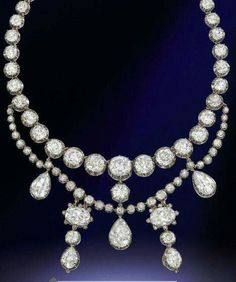 AN ANTIQUE DIAMOND NECKLACE The rivière designed as a graduated line of forty old-cut diamond collets with detachable diamond swags suspending a series of pear and cushion-shaped diamond pendants, two drops may be worn as earrings, mounted in silver and gold, circa 1870, in purple velvet fitted case by Garrard Co. via Christie's