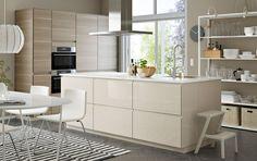 Romslig kjøkken/spiseplass i lys beige og valnøtt med kjøkkenøy og åpen og lukket oppbevaring.