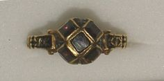Early 17th century.  Gold ring, the transverse cruciform bezel set with four table cut garnets and the back with four triangular panels in black champlevé enamel, the hoop terminating in black enamel volute shoulders