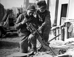 A young French boy helps a machine gunner in Etzling, France