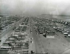 Washington State Historical Society - Aerial view of rows of house trailers arranged along streets in the north section of Richland, WA. Each trailer has a small yard surrounding it, and is covered by an open sided structure. Automobiles are traveling along the roads.  Creator: U.S. Atomic Energy Commission