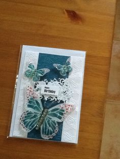 A5 card with white embossed edged background with a coloured central panel with small butterflies. On top is 3D butterflies with clear gems down the middle with a Happy Birthday sentiment.