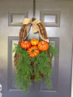 Fall hanging door basket with asparagus ferns, pumpkins, and burlap bow.