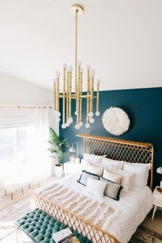 Uplift your simple bedroom decor with some eye-catching lighting that will offer a bold and dramatic centerpiece for the room. Pair simple, neutral colored bedding and furniture with a pop of color with a navy blue-hued accent wall. For a relaxing and inviting space, be sure to have plenty of throw pillows and cozy throws on hand!