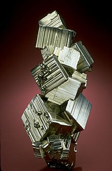 Pyrite. Different growth conditions result in different external shapes of pyrite. This is despite the fact that they are all made up of iron and sulfur atoms linked in the same cubic pattern. The three common shapes of pyrite are: pyritohedron, octahedron, and cube. Cubes tend to grow under low temperatures from solutions with low concentrations of iron and sulfur. Octahedrons and pyritohedrons grow under higher temperatures and more concentrated solutions.