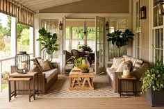 Patio outside of the sun room: source: Southern Living Covered porch with black shutters, lime green garden stool, wicker chairs, powder blue…
