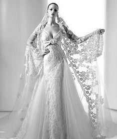 Simply stunning Spanish wedding dress. Elie Saab. The Veil: MANTILLA VEILS ARE BEAUTIFUL MASTERPIECES OF ART. SEAMSTRESSES HAVE HAND-CRAFTED THIS STYLE OF FOR OVER A MILLENIA. SINCE THE VEIL IS CUT ON THE BIAS, IT CREATES A SWEEPING OVER-THE-SHOULDERS LOOK, WHILE DRAPING SOFTLY AROUND THE BRIDE'S FACE. A HAIR COMB IS THEN SEWN AT THE TOP OF THE VEIL, TO SAFEGUARD THE DESIRE LOOK AND KEEP THE VEIL IN PLACE.