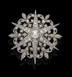 A late 19th century diamond star brooch/pendant. The six-rayed star set throughout with cushion-shaped, rose and old brilliant-cut diamonds, interspersed by similarly-set diamond fleurs-de-lys, mounted in silver and gold
