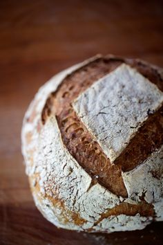 Close-up of handmade whole-grain sourdough bread on wooden kitchen counter.