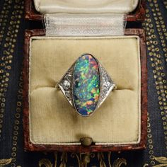 """This cool Edwardian ring is set with a large oval stone, with millegrain detail and diamond accents to the triangular """"wings"""" that flank the opal. It's modelled in white gold and platinum, likely of French origin, and dates to c.1915."""