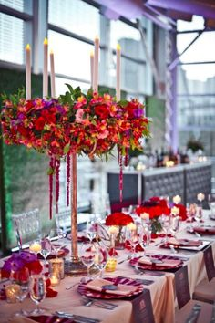 Vibrant floral centerpiece with taper candles photography lindsay