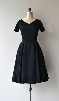 Pretty much perfect 1950s black silk satin dress with surplice bodice, short sleeves, fitted waist and metal zipper. --- M E A S U R E M E N T S ---  fits like: small bust: 38 waist: 26 hip: free length: 42 brand/maker: Miss Couture to ensure a good fit, please read the sizing guide: http://www.etsy.com/shop/DearGolden/policy  ✩ more vintage dresses ✩ http://www.etsy.com/shop/DearGolden?section_id=5986725  ✩ visit the shop ✩ http://www.DearGolden.etsy.com  _____________________ ✩…